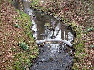 Oil boom in creek-Oil absorbent snake
